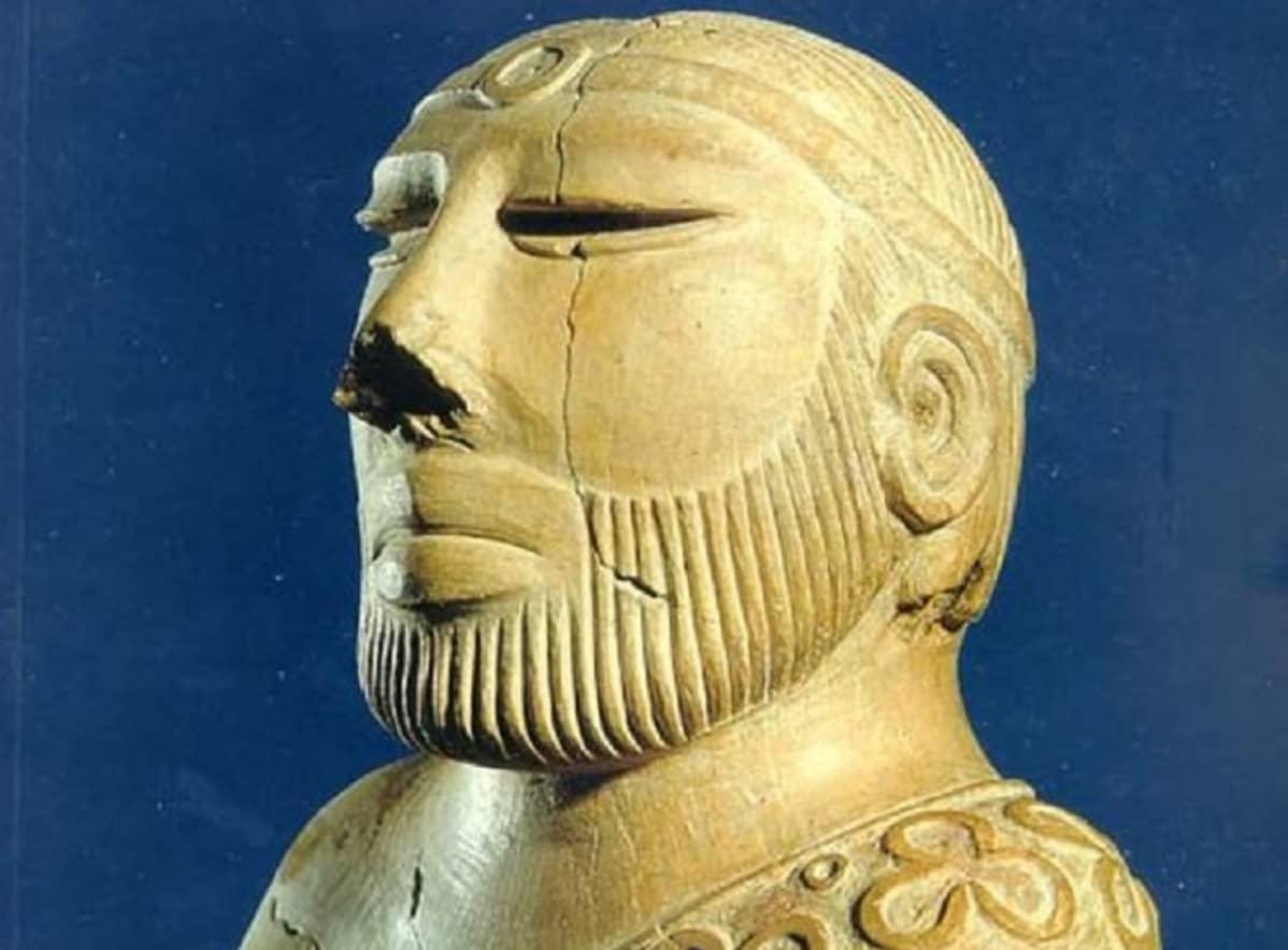 Savipatsas parrakkaasta miehestä, jolla on ornamenttikuviollinen vaate.