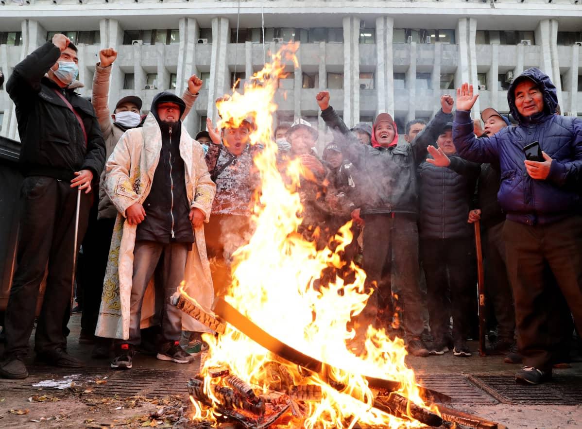 Mielenosoittajia nuotion vieressä, taustalla rakennus.