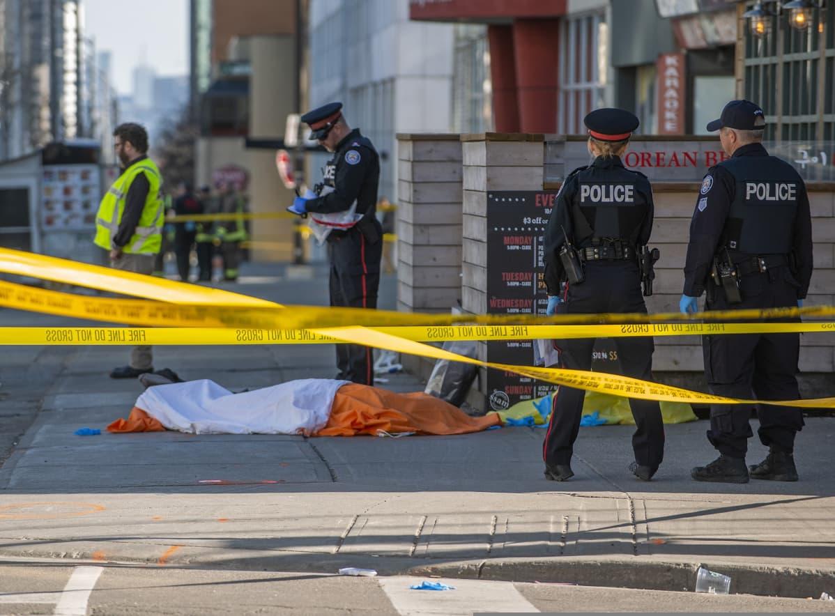 Poliiseja eristysnauhojen takana, kadulla makaa peitetty ruumis.