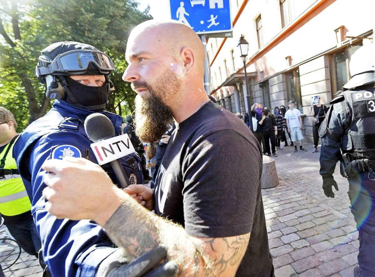 Poliisi estää uusnatsien Pohjoismaisen vastarintaliikkeen NTV-kanavan toimittajana esiintynyttä miestä menemästä vastamielenosoittajien luokse.