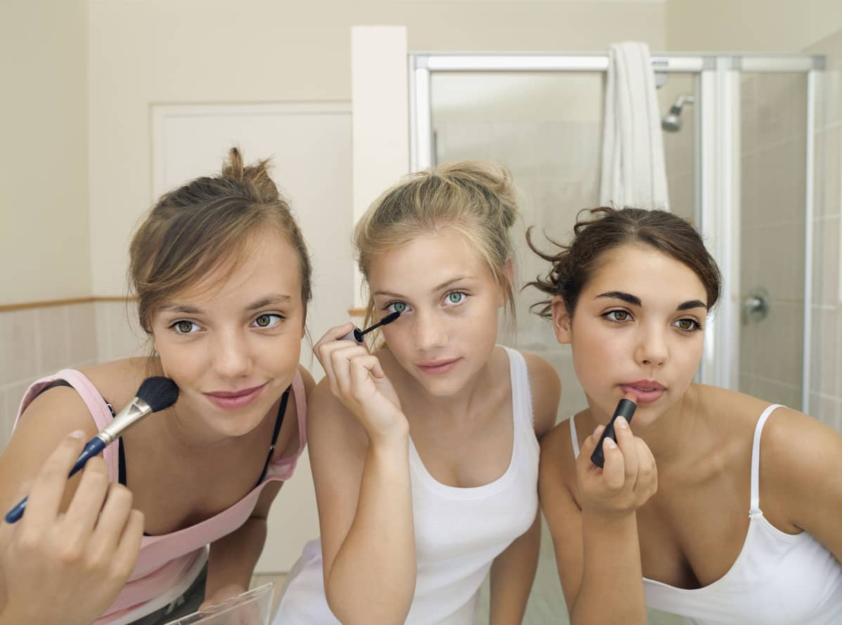 Kolme tyttöä meikkaa peilin edessä.