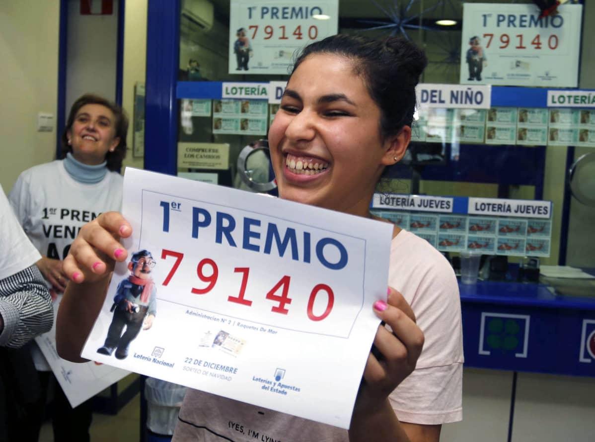Tyttö pitelee paperia, jossa on päävoittoon oikeuttava numero 79410.