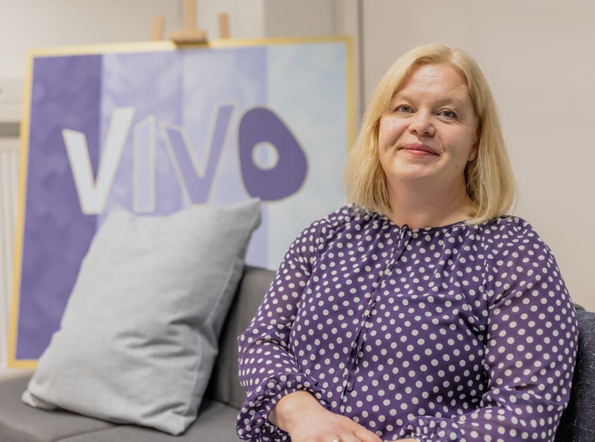 Niina Ojanperä istuu sohvalla. Taustalla Vivo-maalaus.