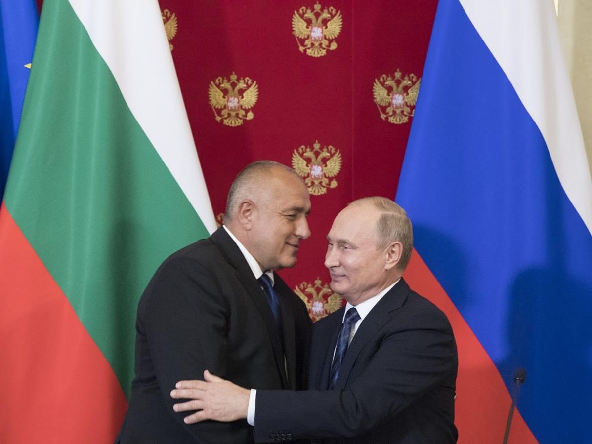 Borisov ja Putin syleilevät. Taustalla ovat Bulgarian ja Venäjän liput ja Venäjän kaksipäistä  vaakunakotkaa esittävillä kuvilla koristeltu punainen kangas.