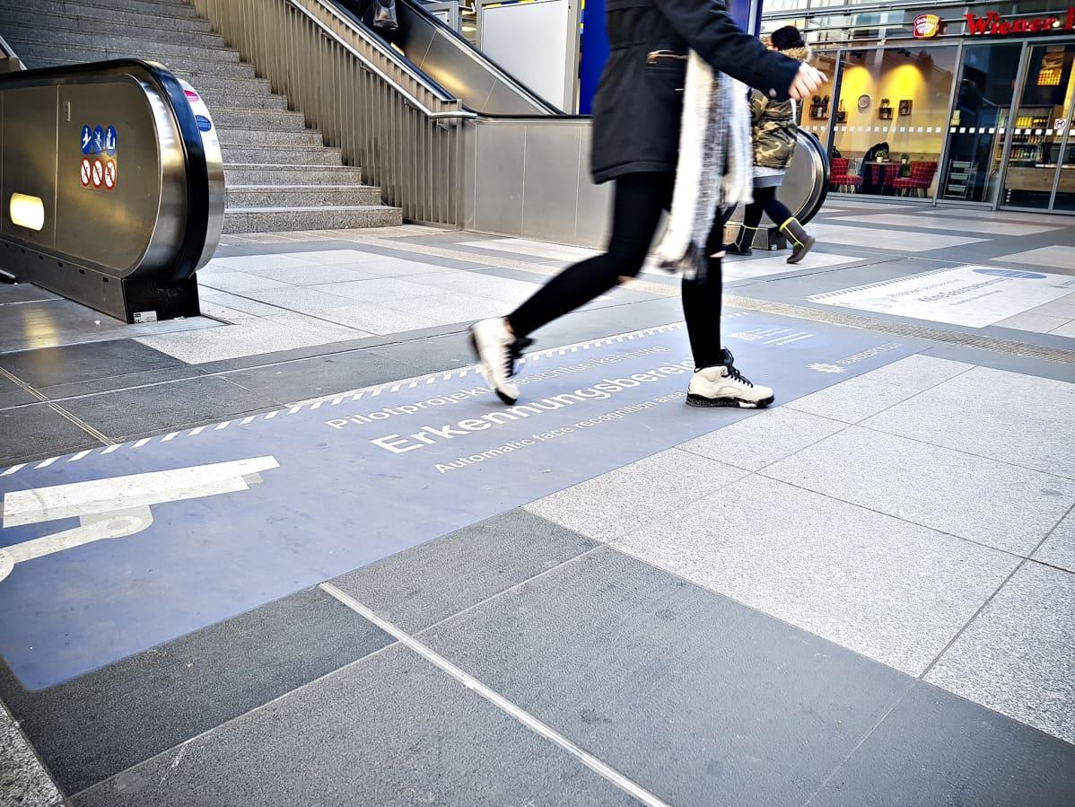 Suuret tarrat Berliinin Südkreuz-aseman lattiassa kertovat, mistä kasvojen tunnistusalue alkaa.  Nainen kävelemässä tarran yli.