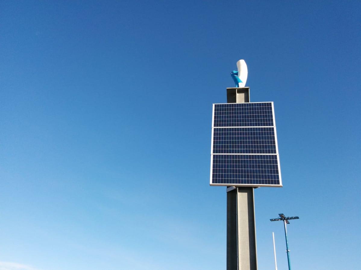 Varoituslaitoksen vieressä olevan harmaan teräspylvään päässä on kolme aurinkopaneelia ja vertikaalilapainen sinivalkoinen tuulimylly.