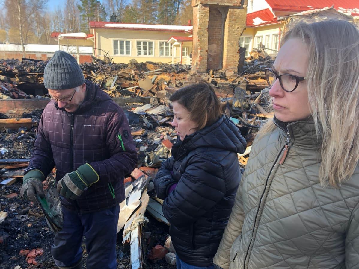 Pekka Ojanen, Tanja Sipilä ja Outi Pennanen tarkastelevat palaneen koulun raunioita.