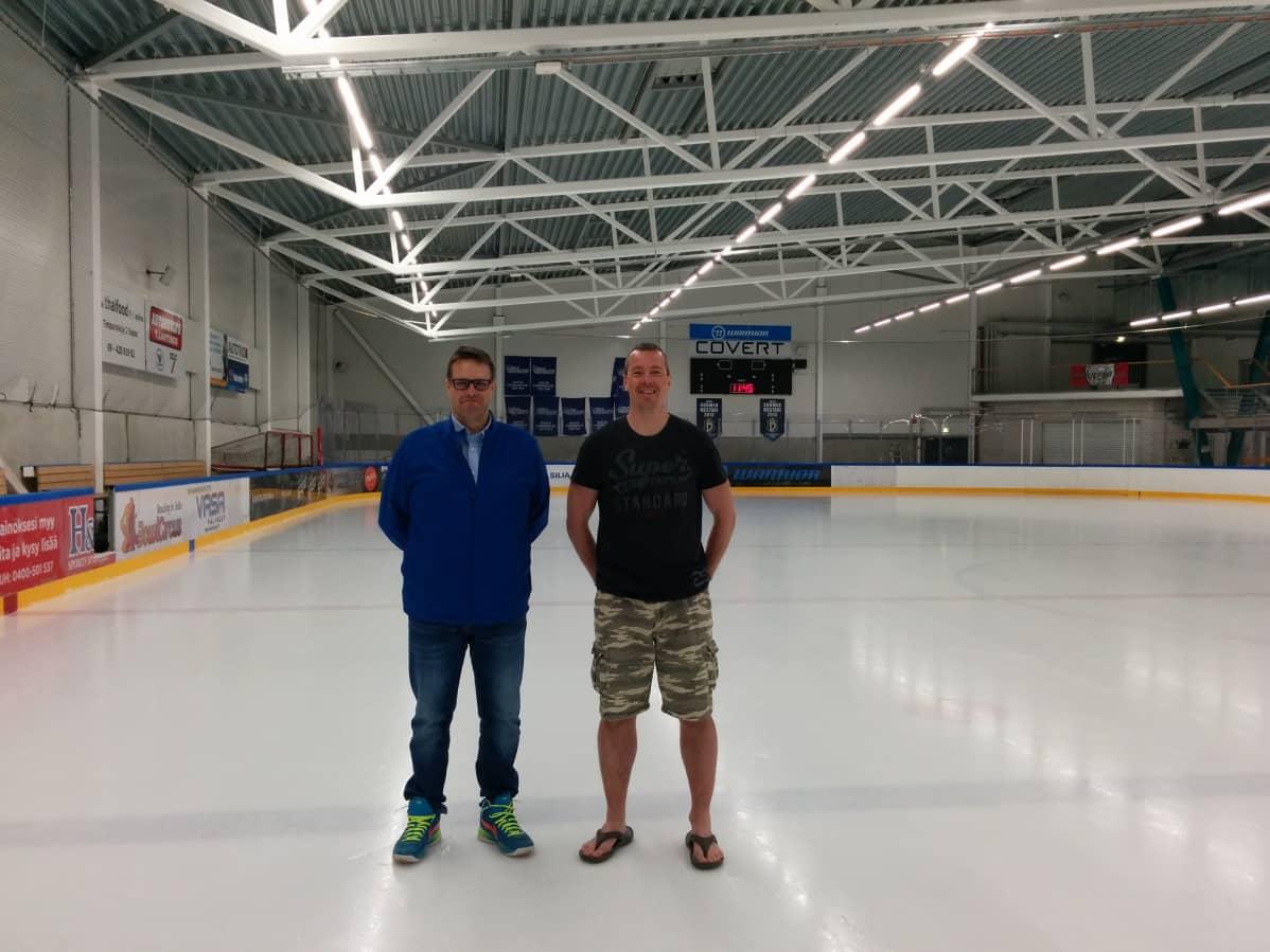 Juhani Pöntinen ja Janne Ahoniemi seisovat Leppävaaran jäähallin kaukalossa jäällä kesävaatteet päällä.
