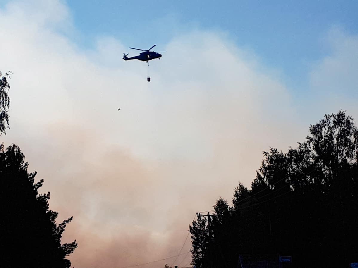 Maastopaloa sammuttaa helikopteri pudottamalla vesilastin maahan.
