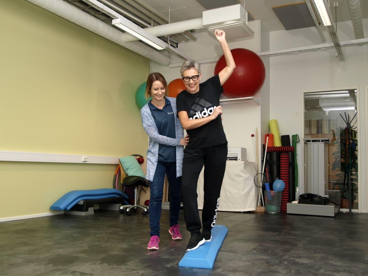 Fysioterapeutti Heidi Kujander on tukena, kun raisiolainen Pia Löfgren ottaa askelia pehmeällä alustalla.