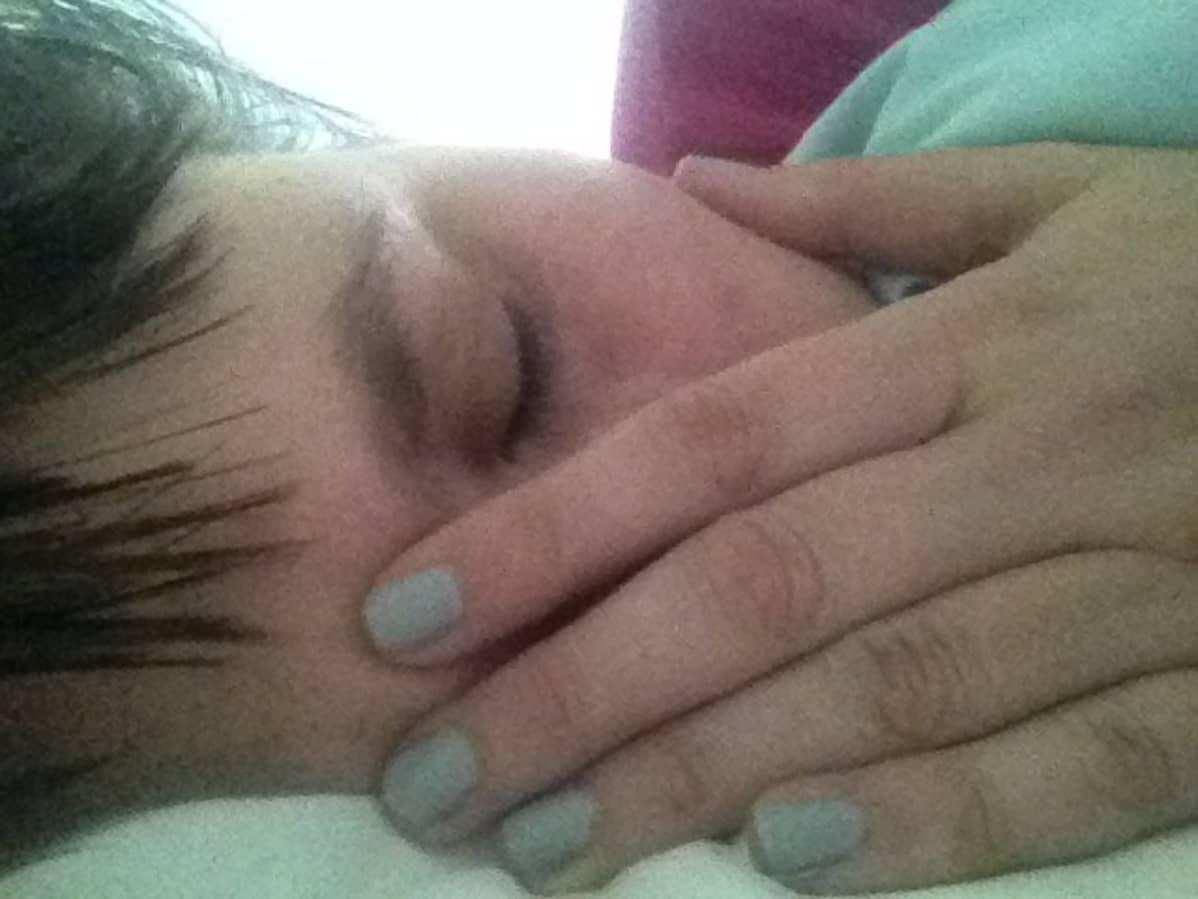 Maaria Oikarinen makaa sängyllä sairaalassa
