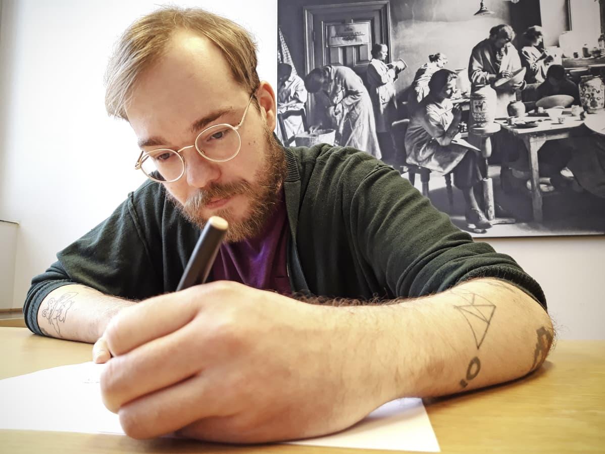 Miikka Lehtonen piirtää paperille