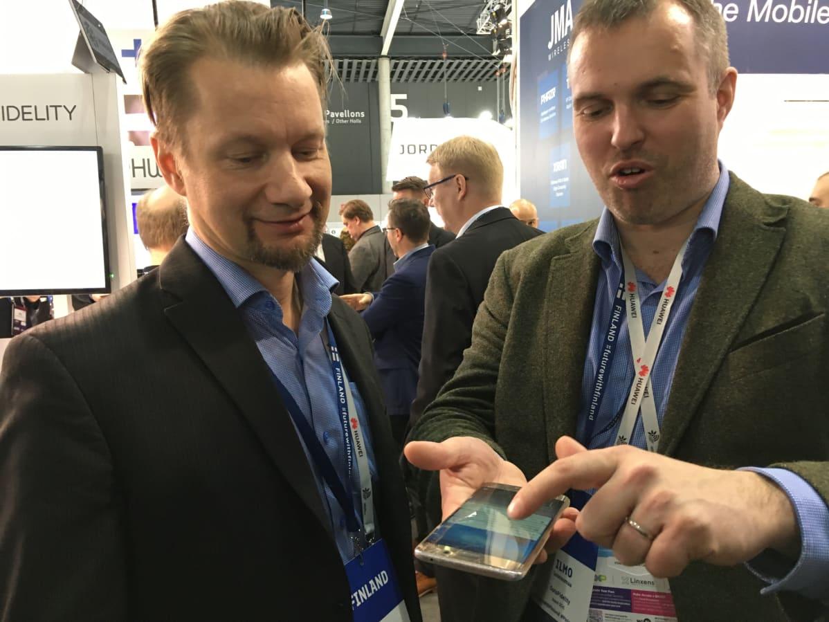 """""""Älypuhelin kestää käyttöä"""", OptoFidelityn Ilmo Lounasmaa sanoo ja osoittaa kolhiintunutta puhelintaan. Vieressä kollega Hans Kuosmanen."""