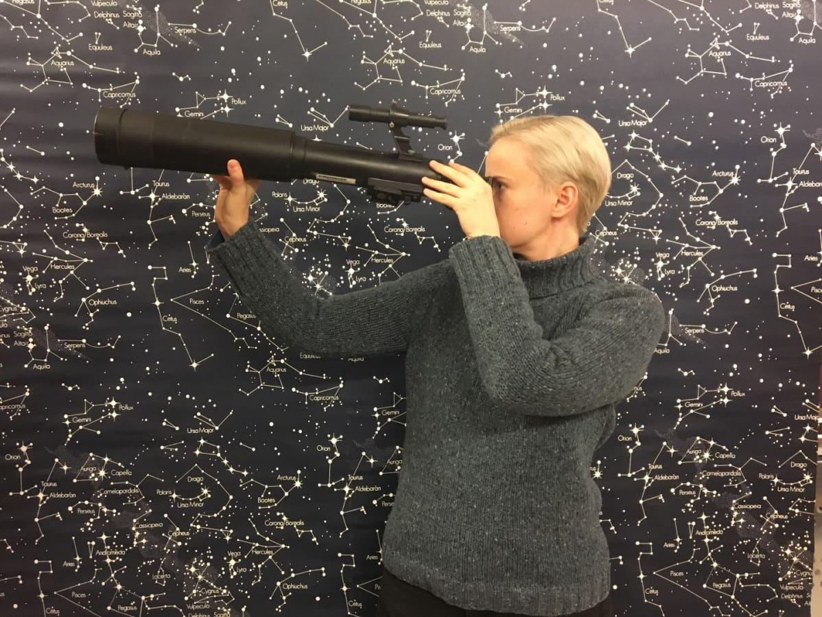 Anne Liljeström katsoo kaukoputkeen taustalla tähtikartta.