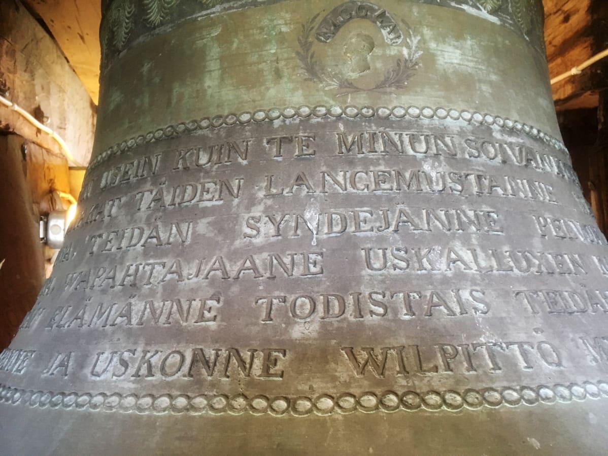 Raamatullista tekstiä lähikuvassa Kangasalan kirkon tornin kellossa