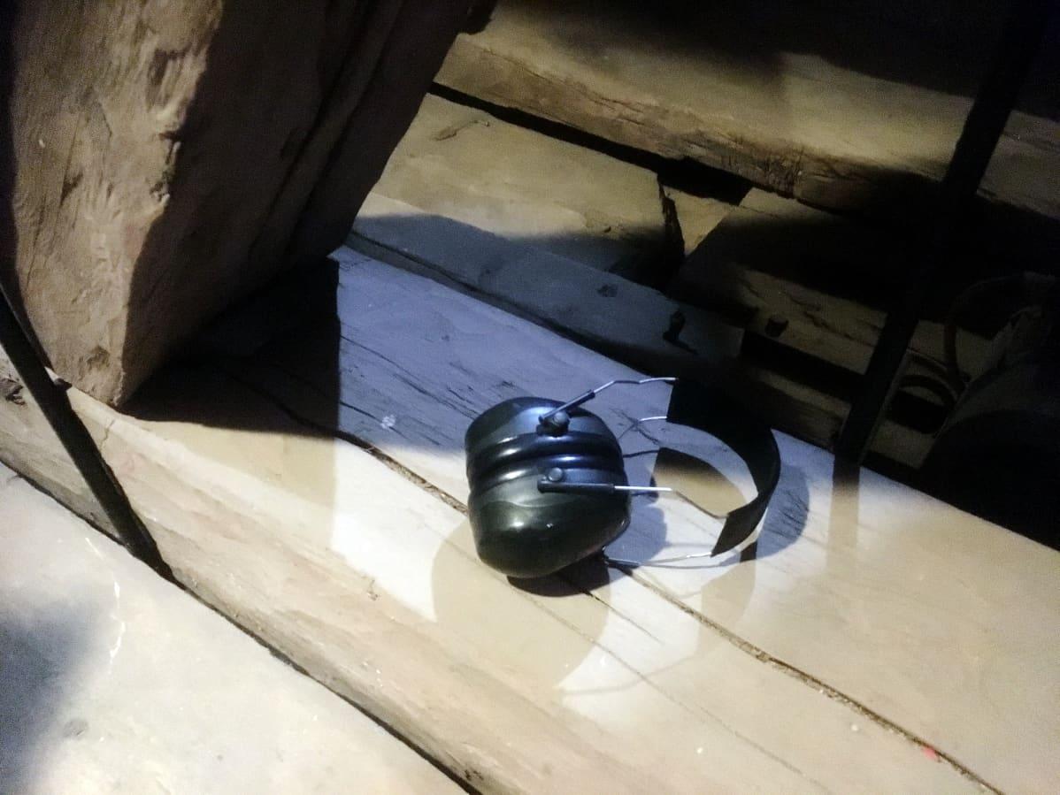 Kuulosuojat kirkon tapulin käsin veistetyistä lankuista tehdyn lattian päällä.
