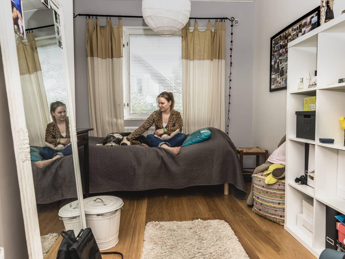 Amalia Paananen istuu sängyllä koiransa kanssa omassa huoneessaan. Huoneessa on suuren suuri peili nojaamassa seinään ja toisella seinällä lokerohyllykkö. Seinällä on kuvia Amaliasta ja hänen kavereistaan.