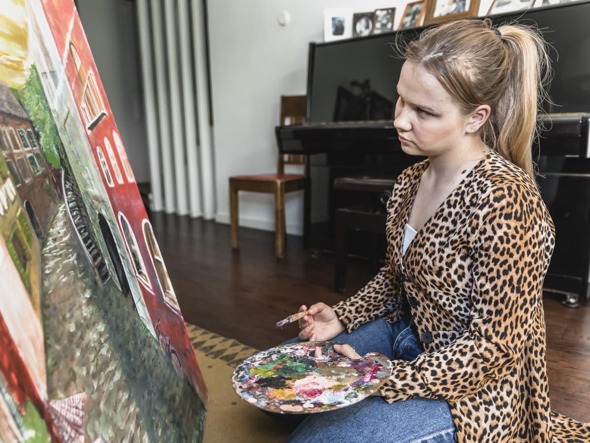 Amalia Paananen istuu polvillaan lattialla maalaustelineen edessä ja maalaa  taulua.l