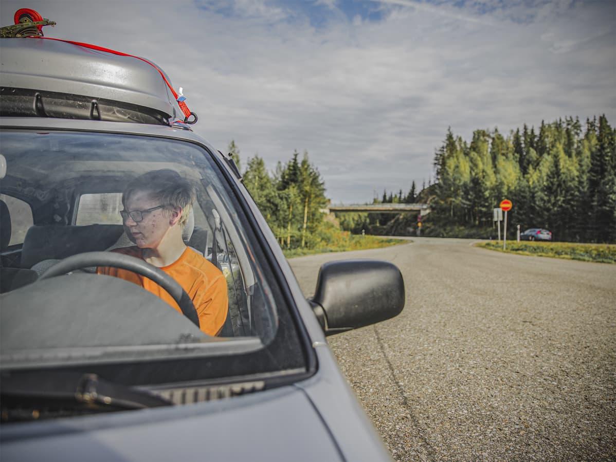 Saku istuu autossaan ja viitostie kulkee ihan vierestä.