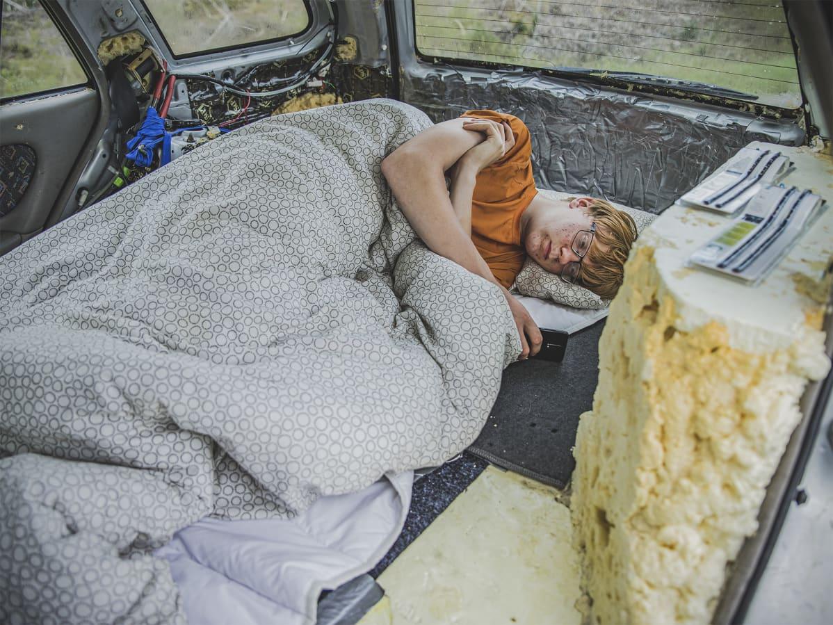Saku nukkumassa autossaan.