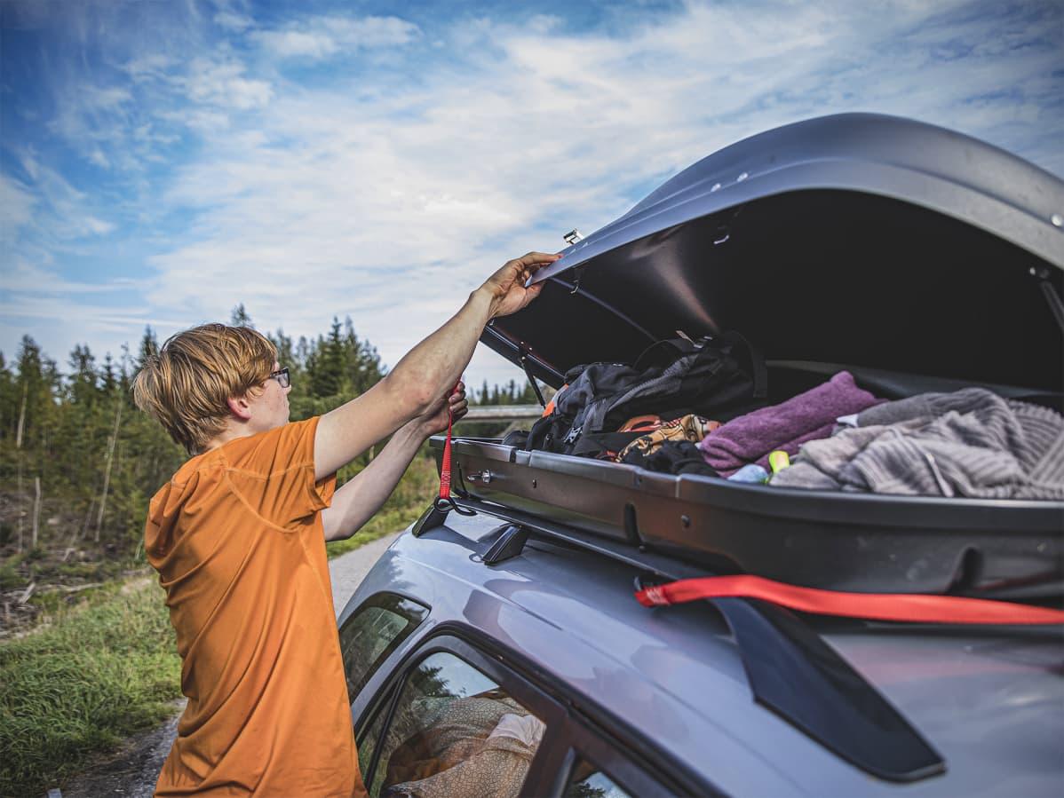 Saku avaa auton katolla olevaa suksiboksia. Boksista näkyy vaatteita ja pyyhkeitä.