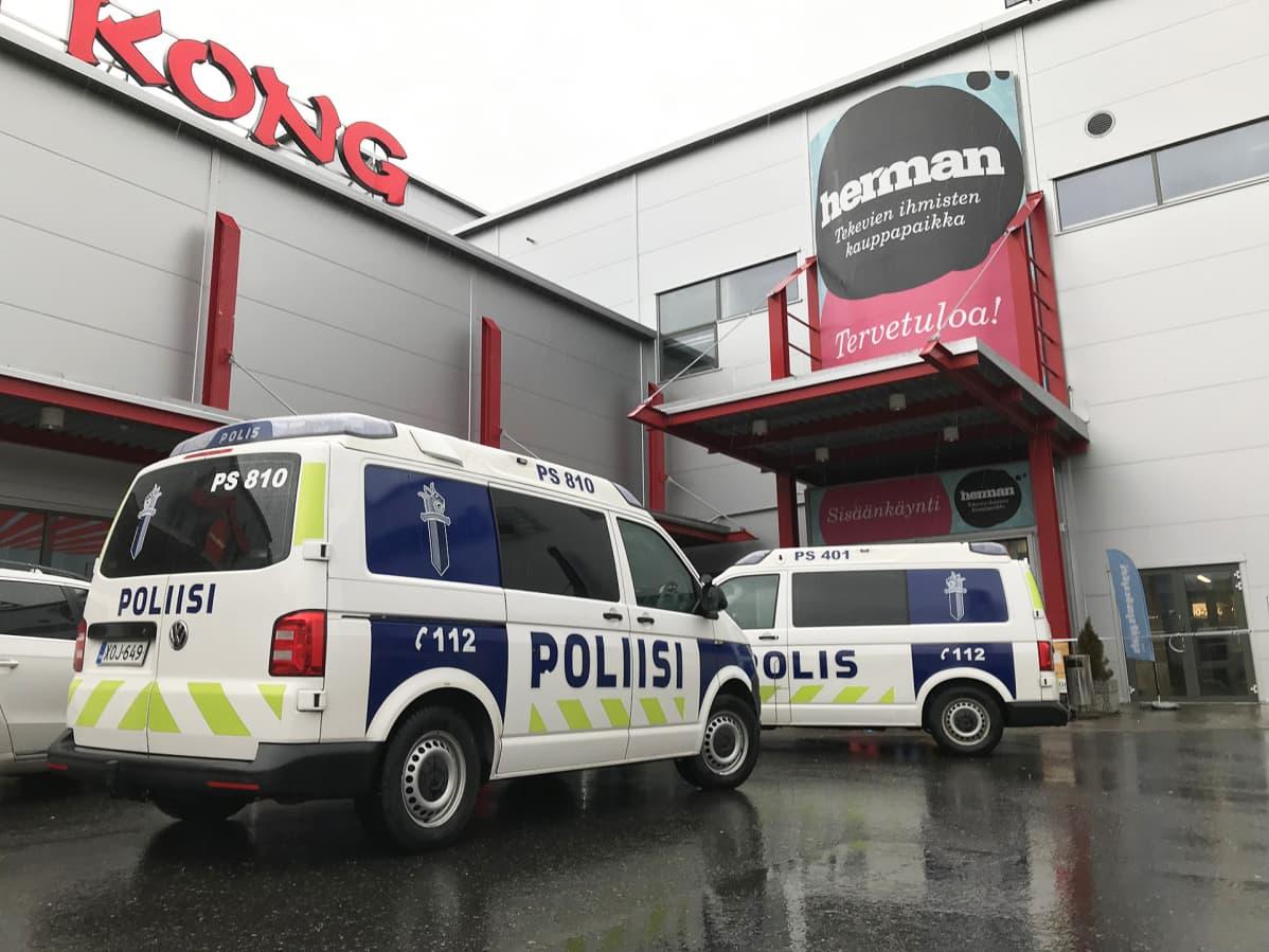 Poliisiautoja kauppakeksuksen edustalla.