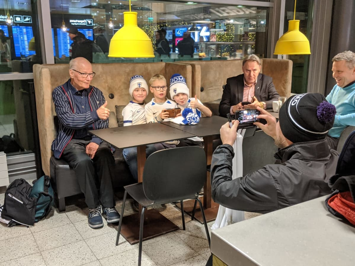 Huuhkajien huoltajalegenda Gunnar Yliharju ja nuoret fanit Atte, Santeri ja Oskari lentokentällä