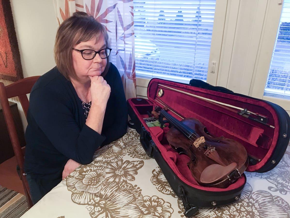 Kotkalainen entinen viulisti Lisa Kallström-Jokipii katsoo vanhaa soitintaan.