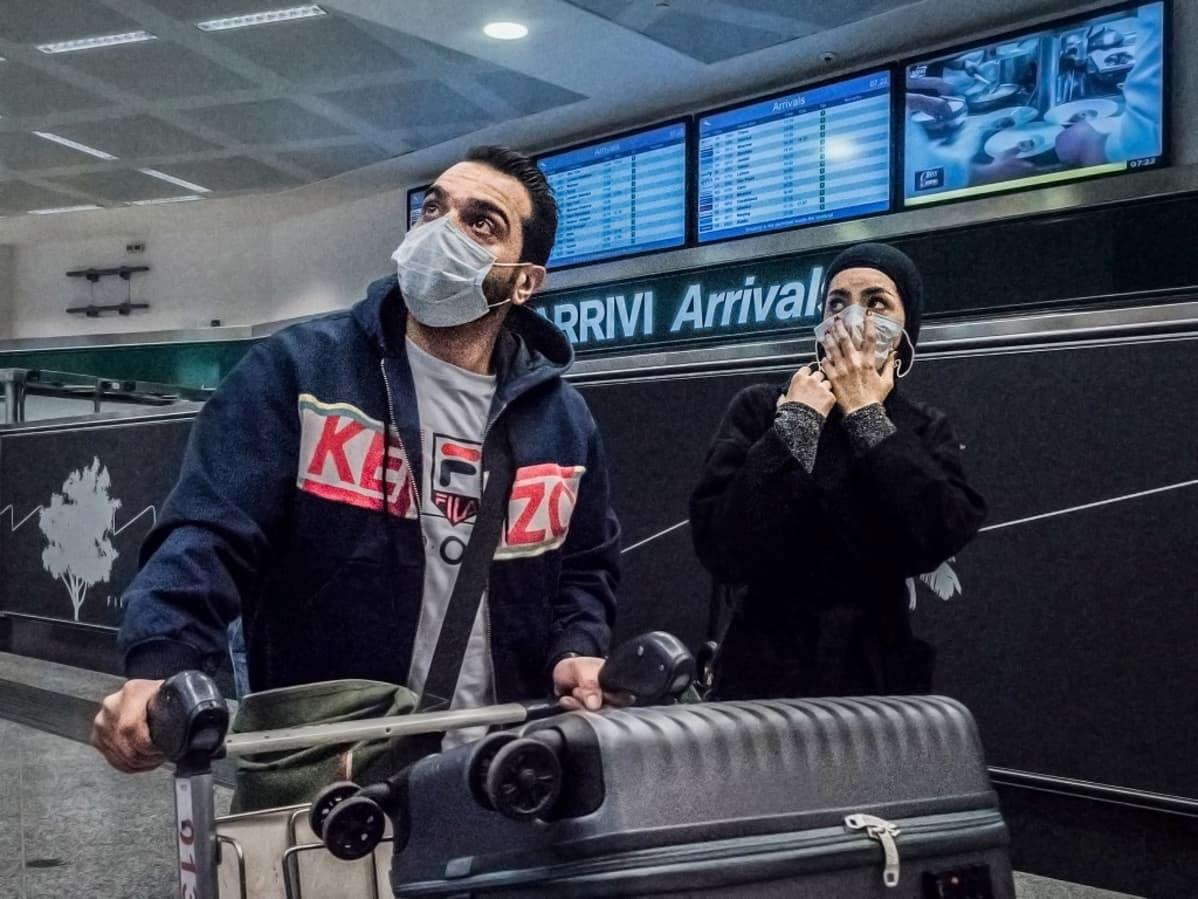 Mies ja nainen matkatavaroineen lentokentällä, molemmilla hengityssuojaimet.
