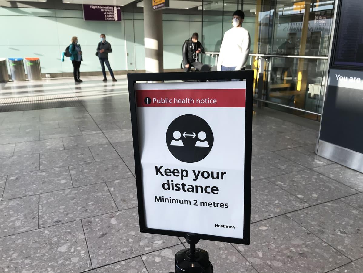 Ilmoitustaulut pyytävät pitämään etäisyyttä muihin matkustajiin.