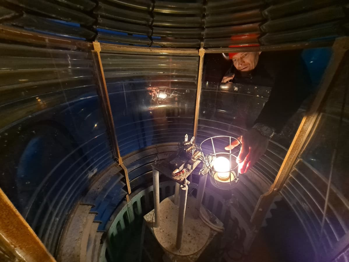 Kallbådan isäntä Veikka Gustafsson asettaa symbolisesti valon alkuperäiselle paikalle Kallbådan majakan lyhtykojussa.
