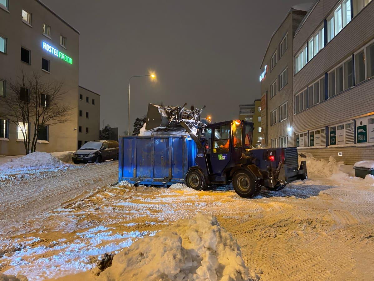 Kauhakuormaaja nostaa lunta siirtolavalle.