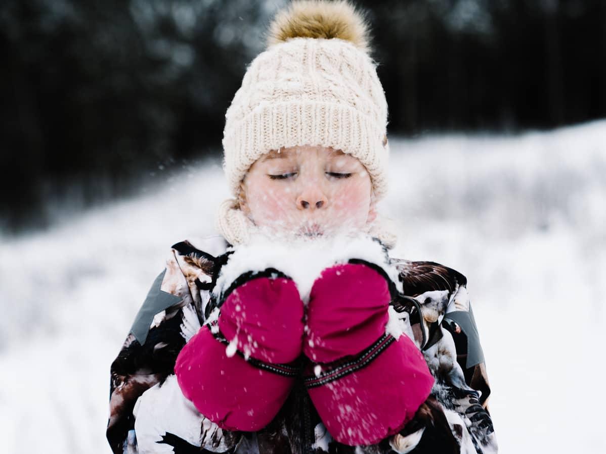 Lapsi puhaltaa lunta.