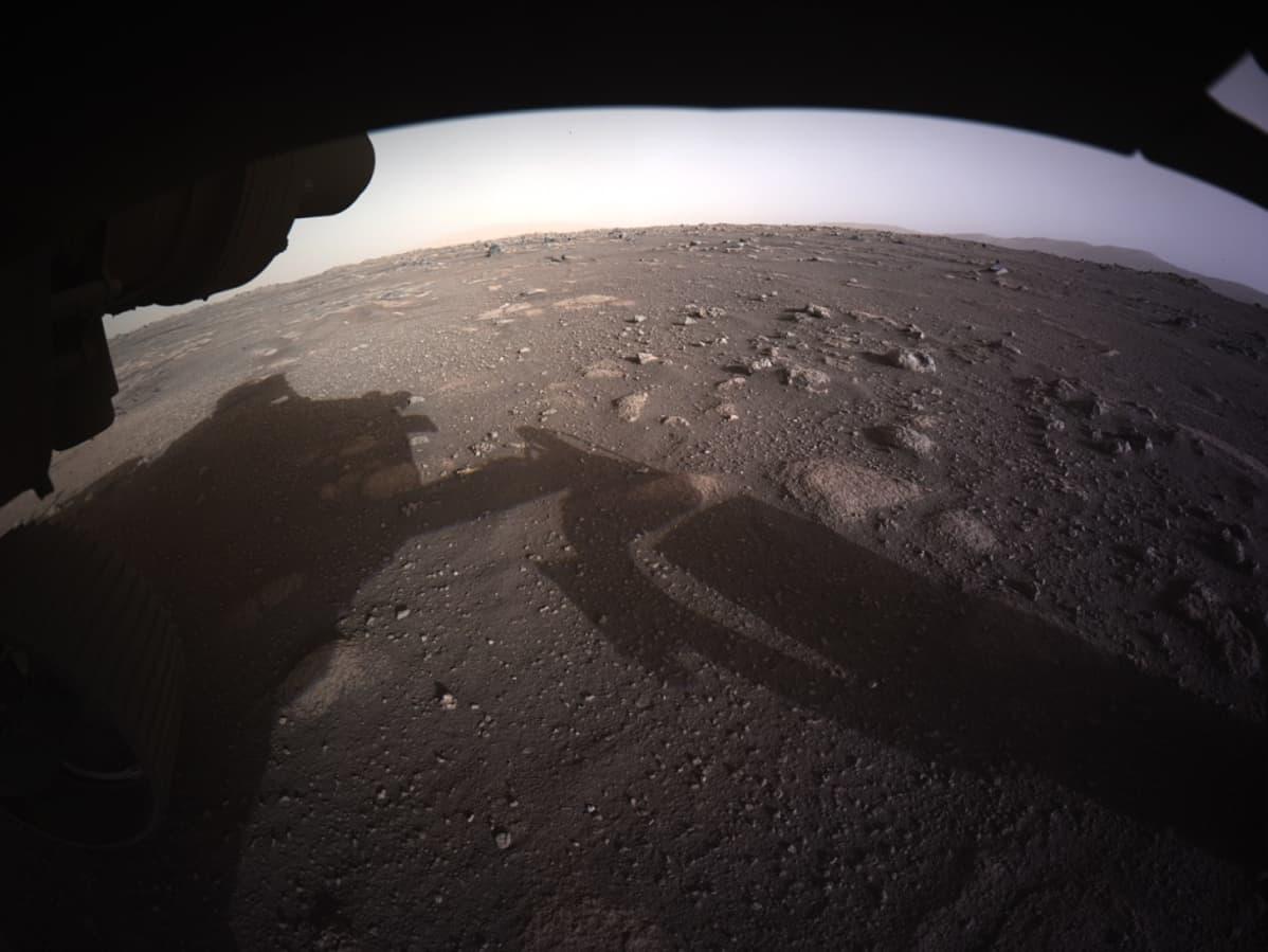 Marsin punainen pinta, jolle heijastuu mönkijä ja sen robottivarsi.