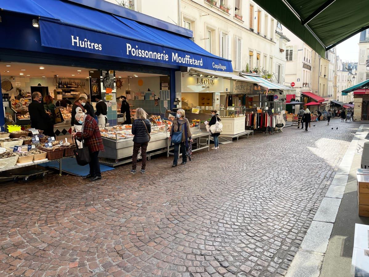Asiakkaat odottelevat tässä hyvin turvavälein vuoronaan rue Mouffetardin eräällä kalakauppiaalla. Useimmiten välit ovat vähän miten sattuu.