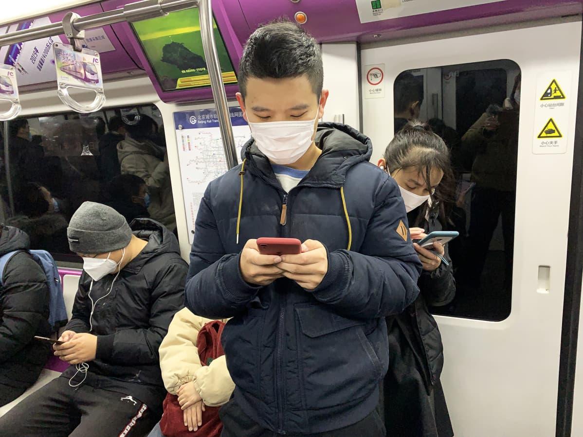 Ihmisiä metrossa.