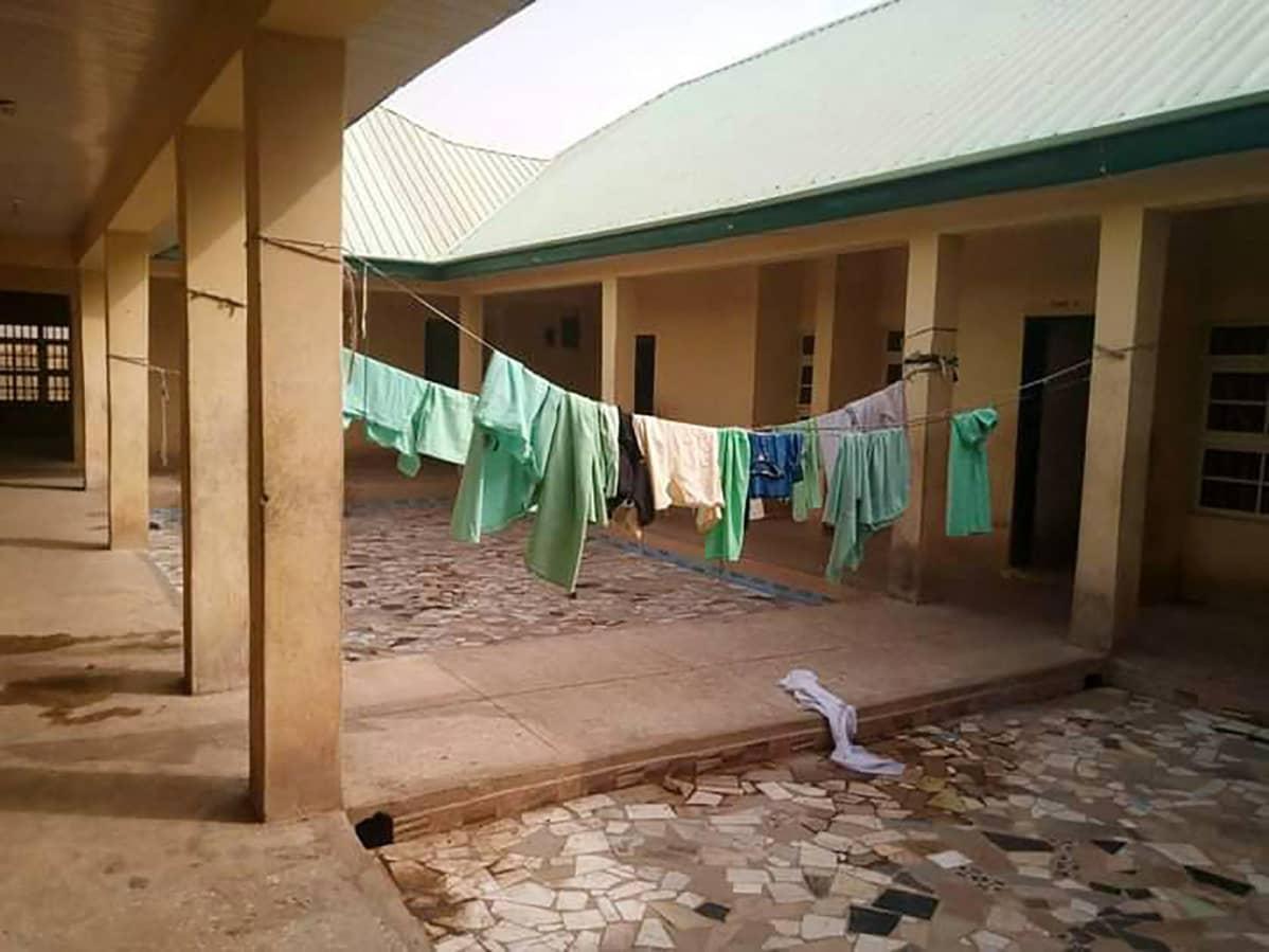 Pyykkejä kuivumassa koulurakennuksen sisäpihalla.