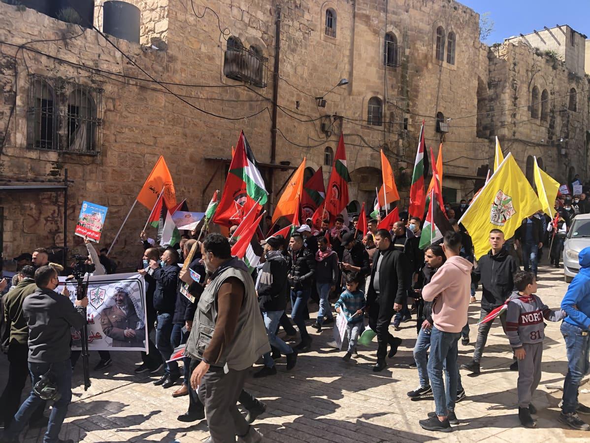 Hebronissa asuvat palestiinalaiset heiluttavat mielenosoituksessa lippujaan