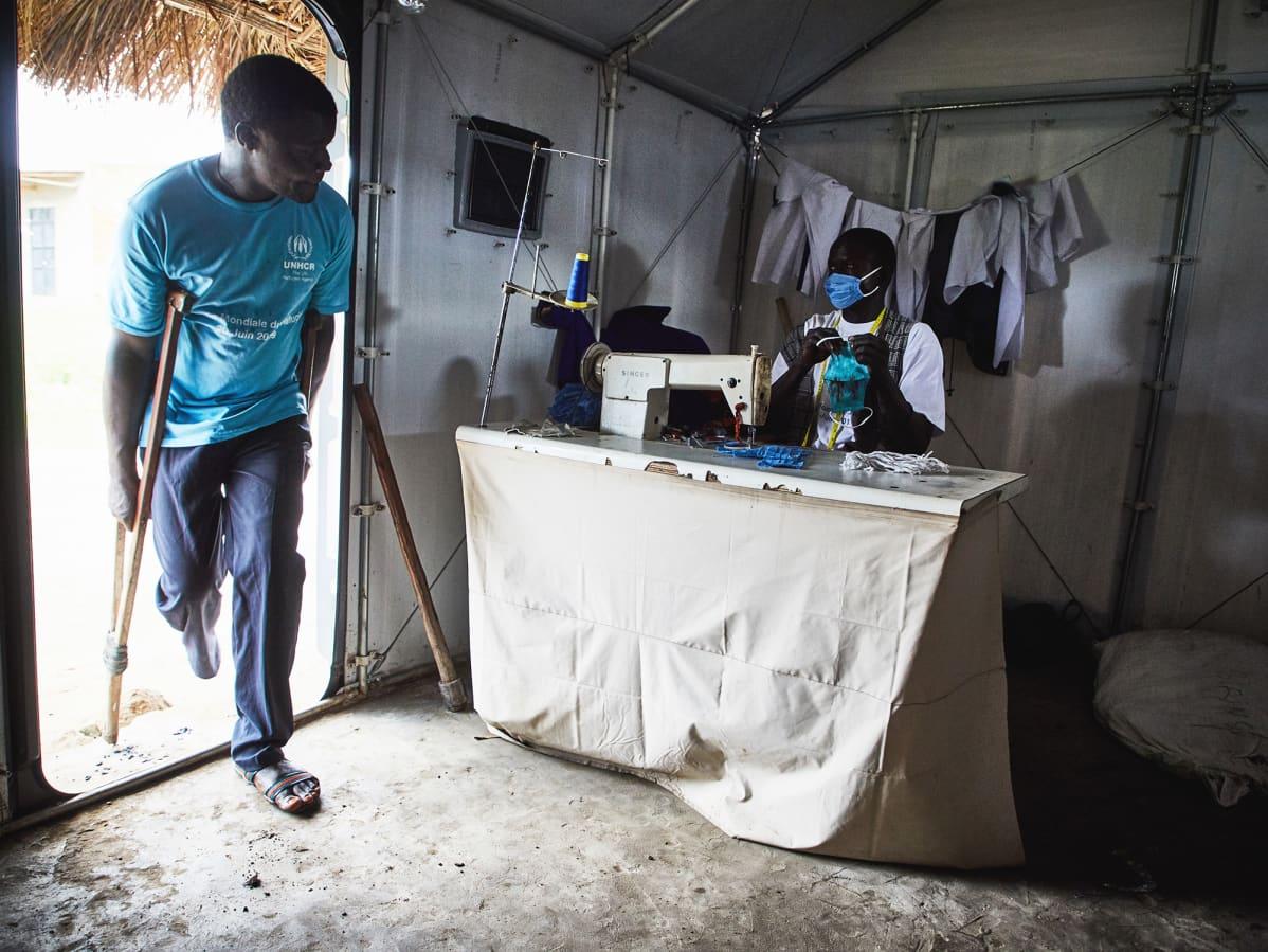 Pakolainen ompelee kasvomaskeja Biringin pakolaisleirissä, Kongon demokraattisessa tasavallassa.