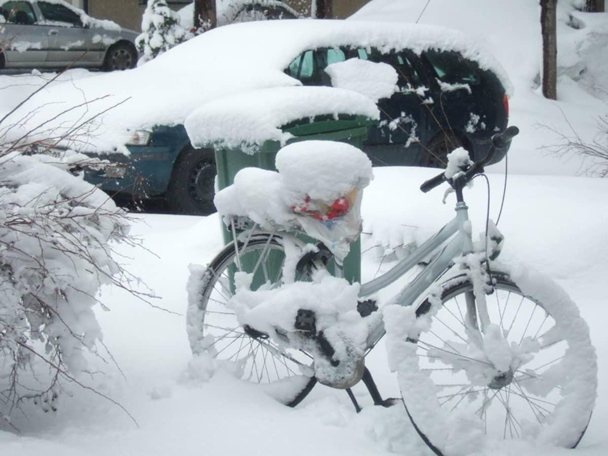 Lumen peittämät auto ja polkupyörä.