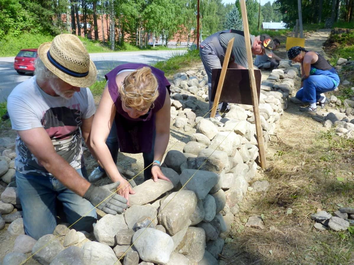 Skotlantilaiset ja juankoskelaiset rakentavat yhteistyössä kiviaitaa Juankosken keskustaan.