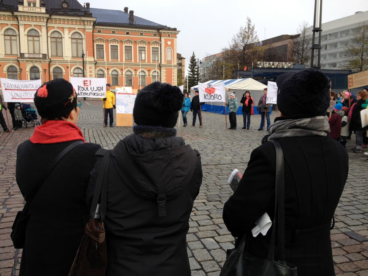 Ihmiset osoittavat mieltään Kuopion torilla.