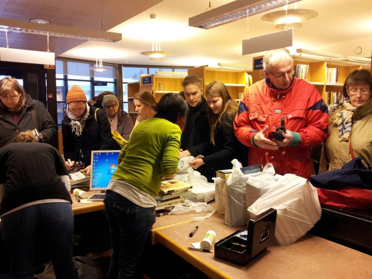 Ihmiset ostamassa poistettavia kirjoja lopetetussa Hyllykallion kirjastossa.