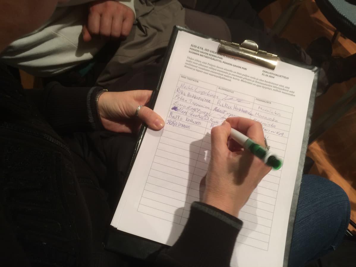 Susi-illan osallistuja kirjoittaa nimensä listaan.