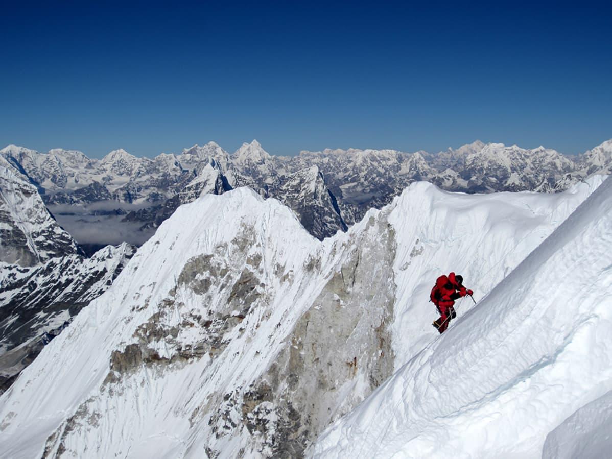 Kiipeilijä lumisella vuorella.