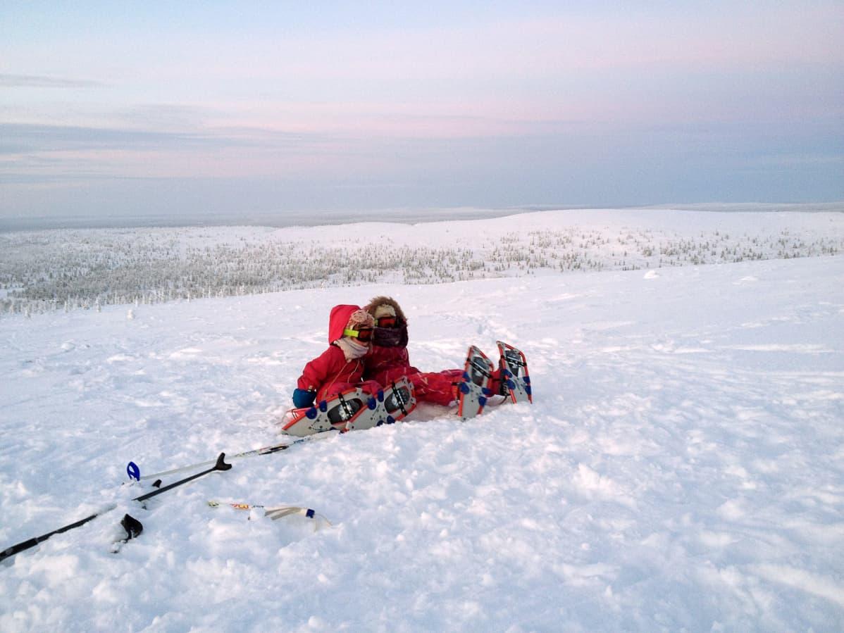 Kaksi lasta istuu tunturissa lumikengät jalassa.