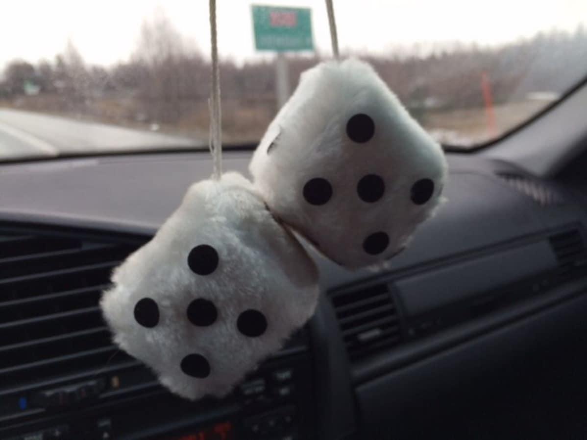 Taustapeilistä roikkuvat karvanopat heilahtelevat autossa.