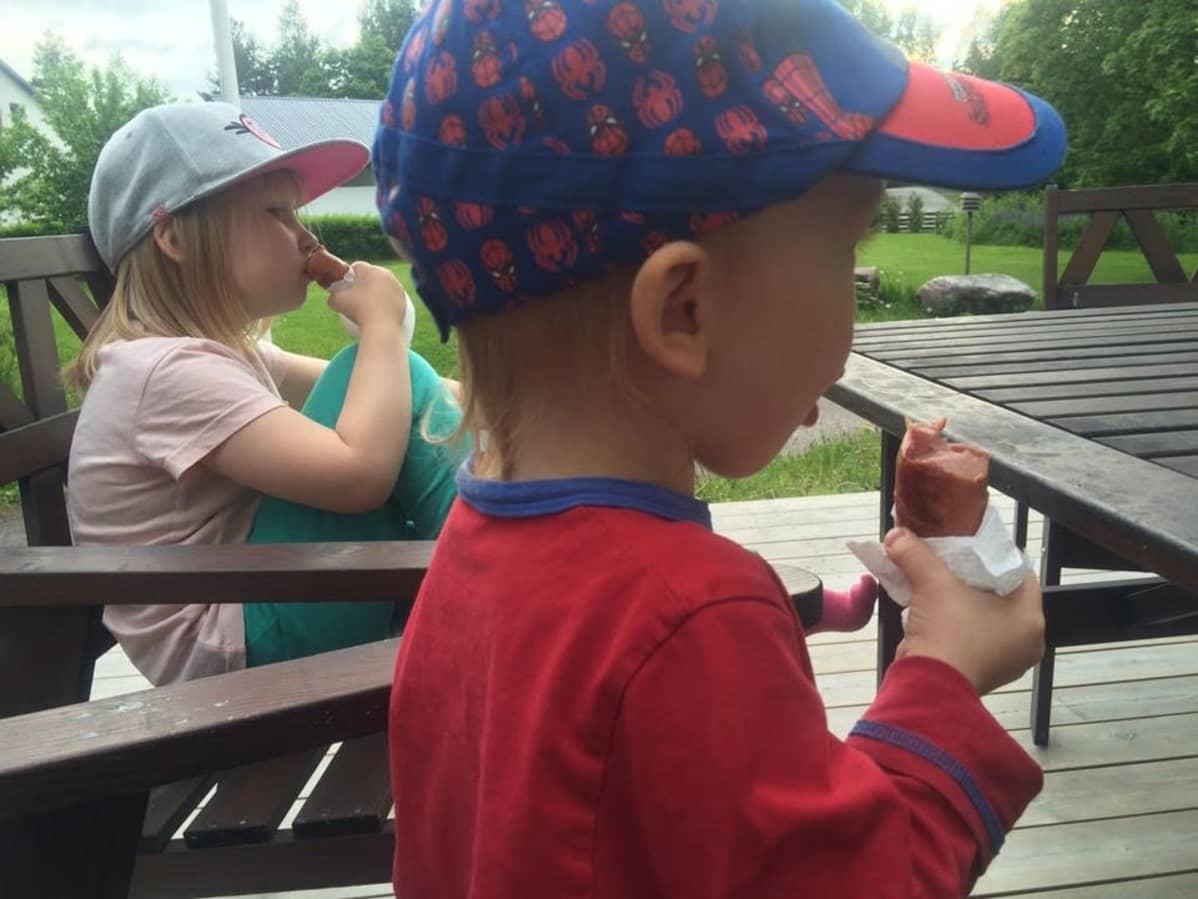 Kaksi lasta syö makkaraa terassilla.