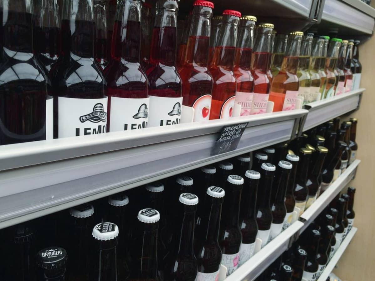 Pienpanimoiden juomapulloja lähiruokaa myyvän kauppa-auton hyllyllä.