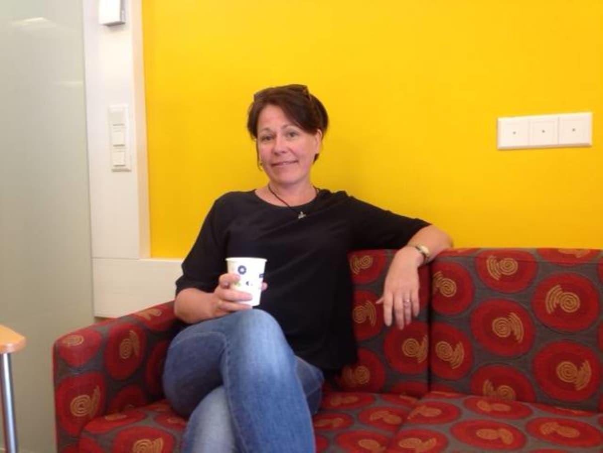Nainen istuu sohvalla kahvimuki kädessään.